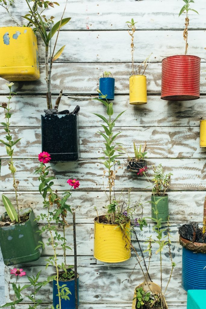paint cans that have been recycled as planters in a vertical garden