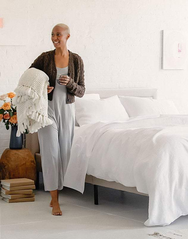 A woman standing next to a bed with an Awara organic mattresses