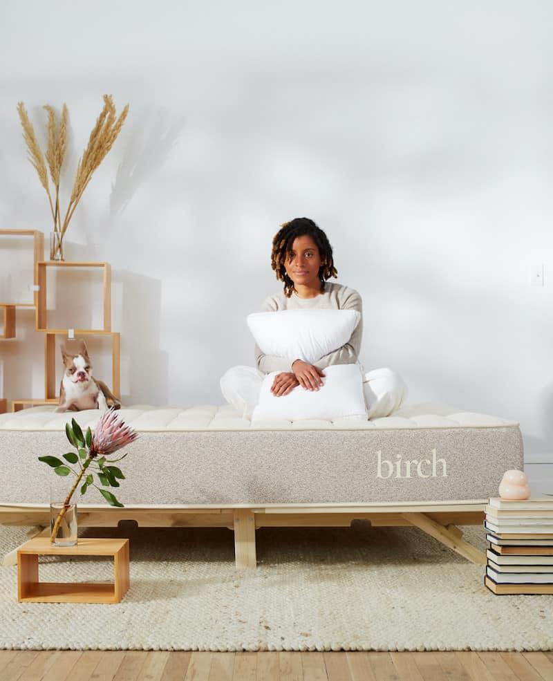 Woman hugging a pillow and sitting on a Birch mattress