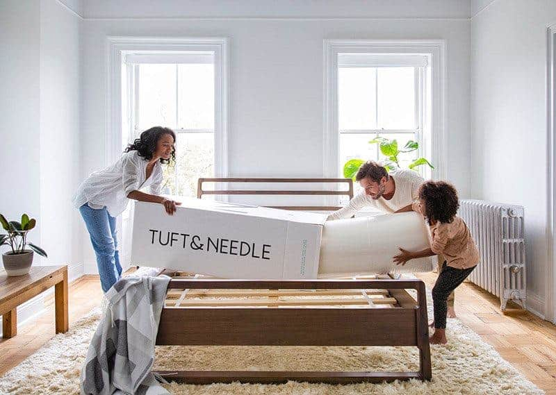 Tuft & Needle bed in a box being unwrapped by a family of three