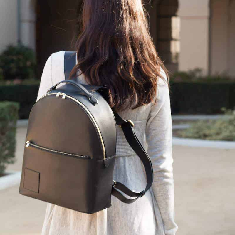 Woman carrying an Opus Mind upcycled backpack