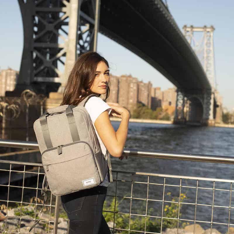 Woman wearing a Solo New York backpack standing in front of Manhattan skyline