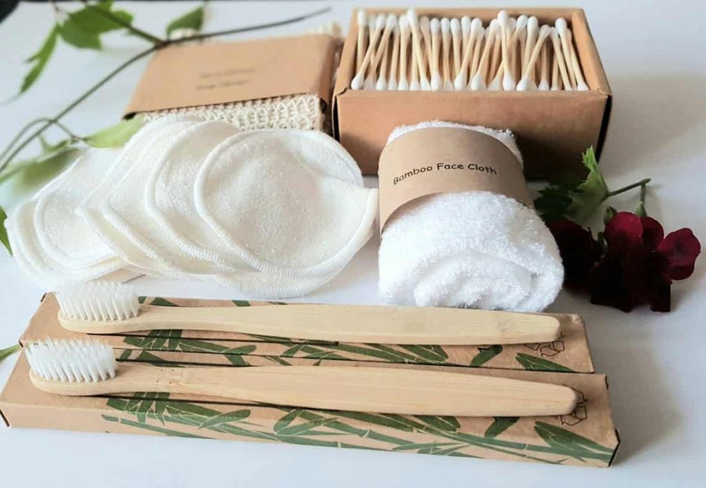zero waste bathroom kit with bamboo toothbrushes, bamboo face cloth, cotton buds, face wipes, and a rose.