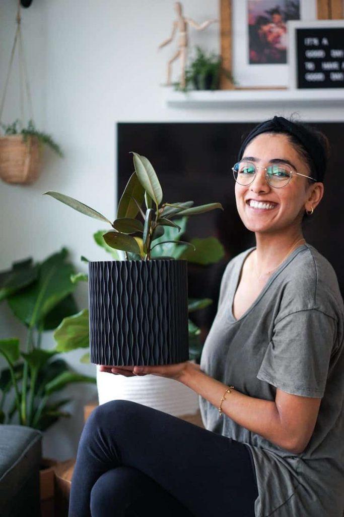 woman holding a large plant pot