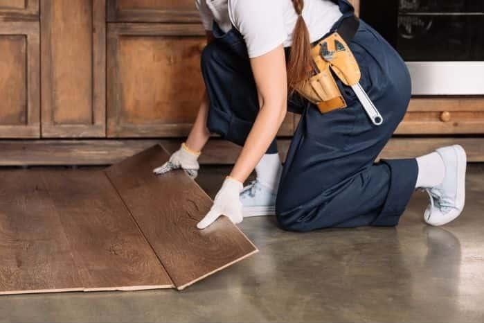woman fixing laminate tiles in her kitchen floor