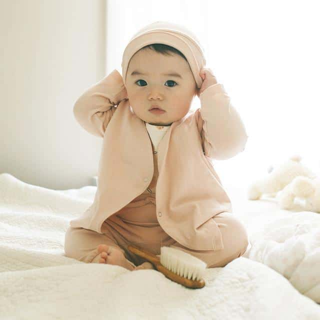adorable baby girl in peach organic baby clothing