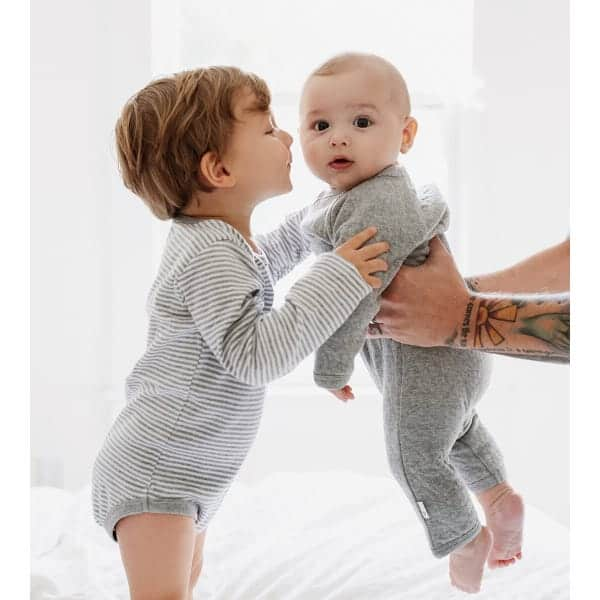 Burt's bees organic baby clothing. older brother being handed younger baby by father